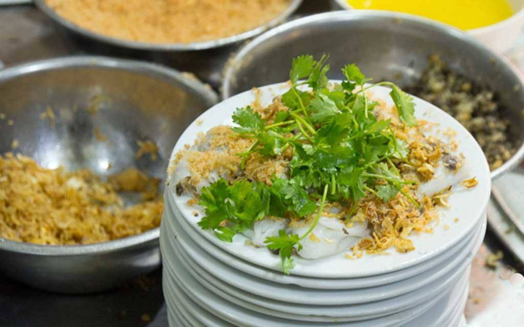 stack of white plates with Bánh cuốn and cilantro, a popular street food in Hanoi, 3 silver mixing bowls of ingredients in background