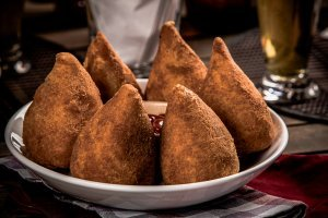 Popular Brazilian foods: Coxinha, a Brazilian snack, with a bar in the background.