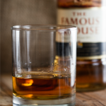 Glass of Famous Grouse whiskey with bottle in the background
