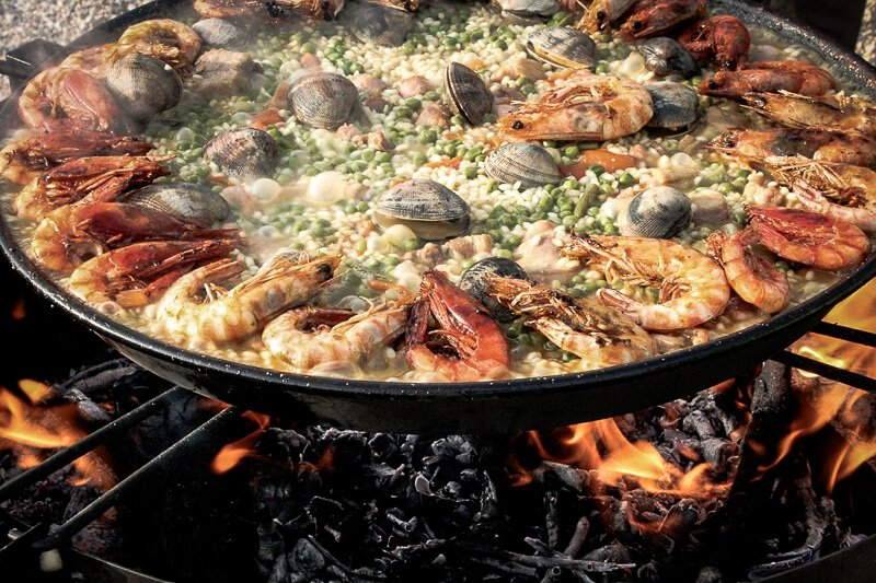 Spanish paella cooking over an open fire