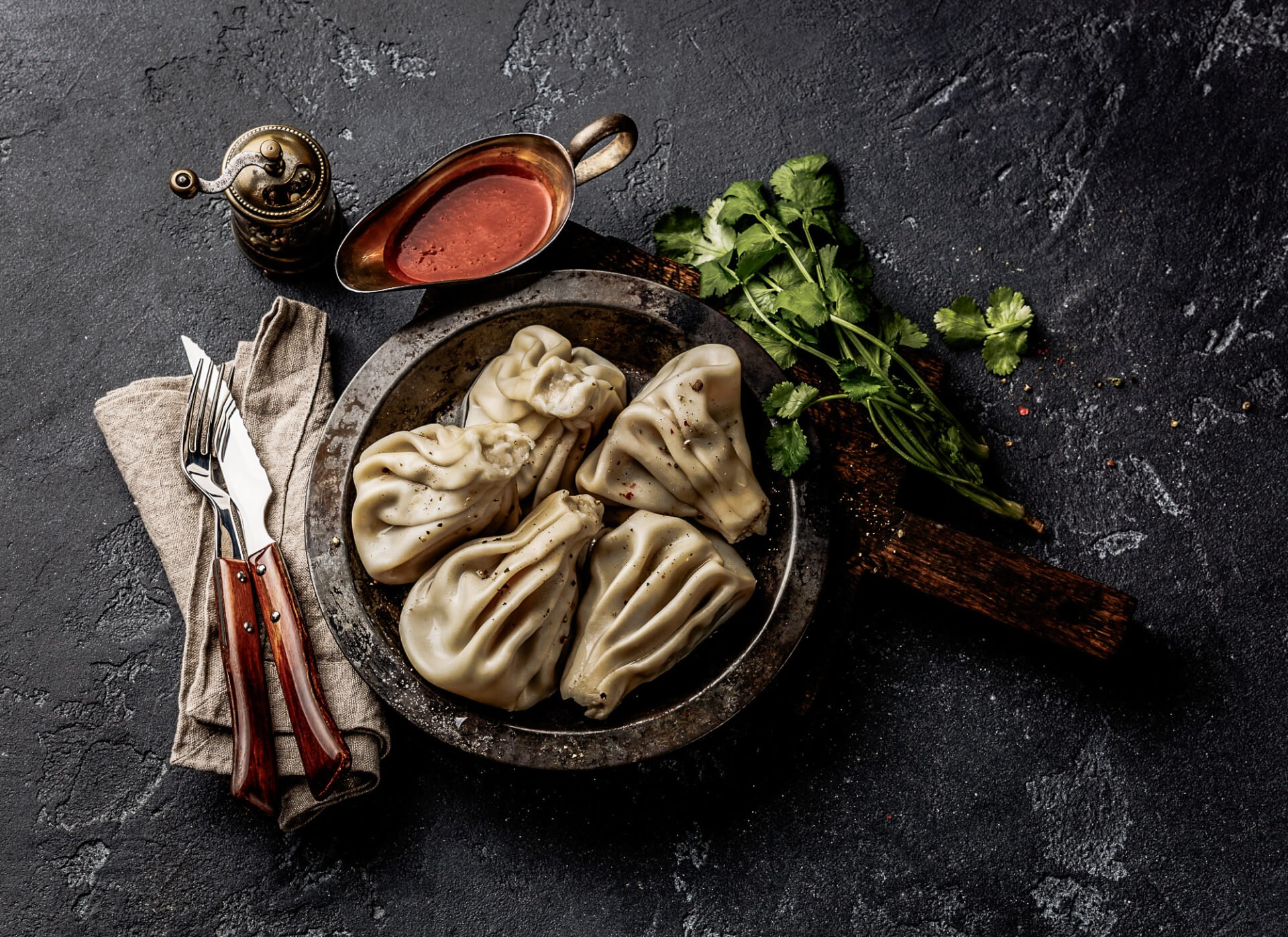 Georgian dumplings Khinkali with meat and tomato spicy sauce satsebeli on dark stone background